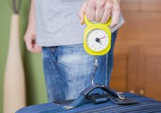 Man checking luggage weight with steelyard balance. Man checking hand luggage weight using a steelyard balance by low cost airlines restrictions Royalty Free Stock Photography
