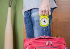 Man checking luggage weight with steelyard balance. Man checking hand luggage weight using a steelyard balance by low cost airlines restrictions Stock Photography