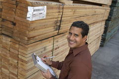 Man Checking Lumber In Warehouse Royalty Free Stock Image