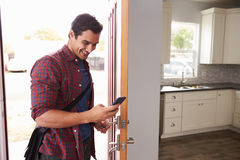 Man Checking Mobile Phone As He Opens Door Of Apartment Stock Image