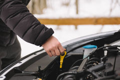 Man checking oil level in his car using dipstick Royalty Free Stock Images