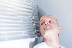 Man checking out of the blinds. Senior man at home checking out of his window if there is something or someone to fear Stock Photo