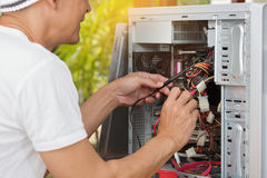 Man checking power signal of tower PC with meter probes of digital meter. Royalty Free Stock Image