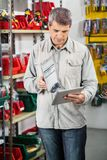Man Checking Product Through Digital Tablet. Mature man checking product through digital tablet in hardware store Stock Images