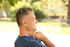 Man checking pulse outdoors. On sunny day royalty free stock image