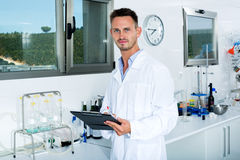 Man checking quality of wine in chemical laboratory Stock Photography