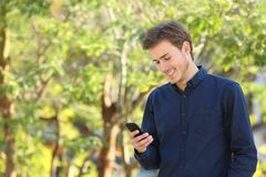 Man checking smart phone in a park royalty free stock photography