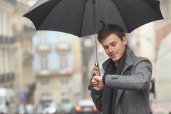 Man checking smartwatch under the rain in winter. Man checking smartwatch under the rain walking in the street in winter stock images