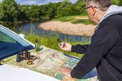 A man checking the terrain on a map with a compass stock photo