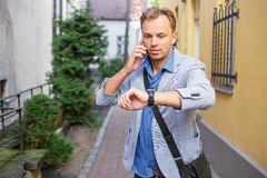 Man checking time on his watch and talking on the phone Royalty Free Stock Photos