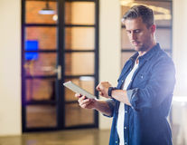 Man checking time while holding tablet in office. Man checking time while holding digital tablet in creative office Royalty Free Stock Photos