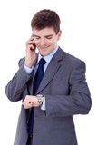 Man checking time while speaking on cellphone Stock Photo