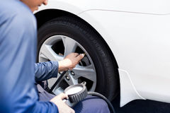 Man checking tire air pressure. With gauge Royalty Free Stock Image