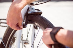 Man checking a wheel on his bike Stock Photos