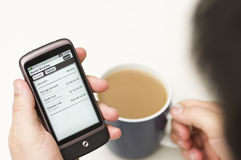 Man checks Banking details on a Smartphone. A man checks his bank using mobile banking over a coffee Stock Photography