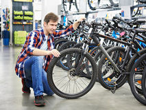 Man checks bike before buying in shop Royalty Free Stock Image