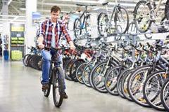 Man checks bike before buying in shop Royalty Free Stock Photos
