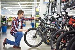 Man checks bike before buying in shop Royalty Free Stock Photo