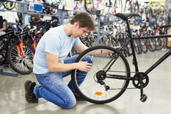 Man checks bike before buying in sports shop Royalty Free Stock Photos