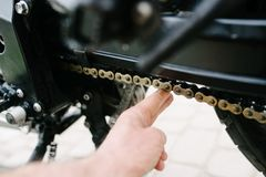Man checks the chain tension in motorcycle Royalty Free Stock Photography
