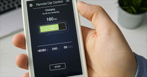 Man checks charge level of his car. Charging in progress Car remote control using smartphone application fictional