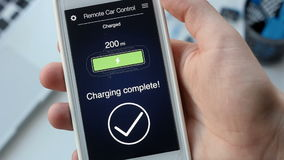 Man checks charge level of his electric car. Battery is charged. Car remote control using smartphone application