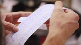A man checks a check from purchases in a supermarket. Spending calculations Hands close up