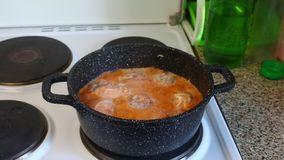 A man checks the cooking of meatballs in boiling sauce. He removes the lid and returns it to its place. A man checks the cooking of meatballs in boiling sauce stock video