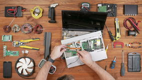 A man checks the details of a laptop with a multimeter. Disassembled computer, a wooden table top view. Touch the stock video footage