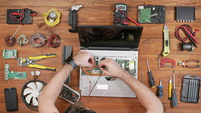 A man checks the details of a laptop with a multimeter. Disassembled computer, a wooden table top view. Touch the stock footage
