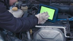 The man checks the engine using the touchpad with greenscreen. The man looks in the touchpad with greenscreen and checks the engine in the car stock footage
