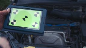 The man checks the engine using the touchpad with greenscreen. The man looks in the touchpad with greenscreen and checks the engine in the car stock video footage