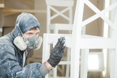 Man checks the evenness of the paint application in respiratory mask. Application of flame retardant ensuring fire. Protection, airless spraying device Stock Photos