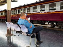 A man checks his mobile phone at Bangkok train station royalty free stock photos