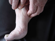 Man checks his sore foot. Man's hands on his painful foot Royalty Free Stock Photo