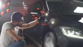 Man checks result of polishing of car with a flashlight. stock footage