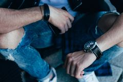 The man checks the time. in ragged jeans and a black jacket, street style. man`s hand with a watch. and in the other hand holds a royalty free stock photo