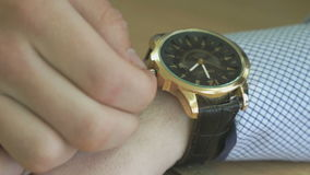 The man checks the time of the wristwatch stock video