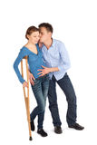 Man Cheer Up Woman. Gentle man cheer up his injured girlfriend using crutch to walk isolated on white stock image