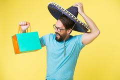 Man cheerful face sombrero hat holds shopping bag yellow background. Guy with beard festive in sombrero. Man festive. Mood holds shopping bag. Seasonal sale and royalty free stock photos