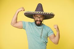 Man cheerful face in sombrero hat posing with biceps muscles strong gesture yellow background. Mexican party concept. Guy looks festive in sombrero. Party and stock image