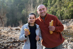 Man and cheerful woman eating sandwitches at picnic outdoors Royalty Free Stock Photos