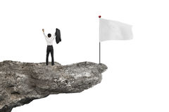 Man cheering on cliff with blank flag and white Stock Photography