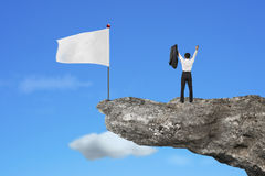 Man cheering on cliff with blank white flag and sky Stock Photo