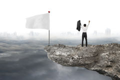 Man cheering on cliff with white flag and cloudy cityscape Stock Image