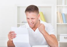 Man cheering in jubilation as he reads a letter. Punching the air with his fist as he reads the good news stock photos