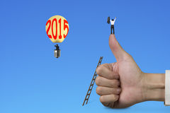 Man cheering on thumb up with 2015 hot air balloon Stock Image
