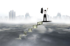 Man cheering on top of money stairs cityscape cloudscape Royalty Free Stock Image