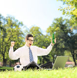 Man cheering and watching soccer on a laptop in the park Stock Photography