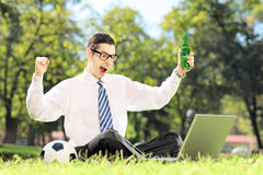 Man cheering and watching soccer on a laptop in a park Stock Photo
